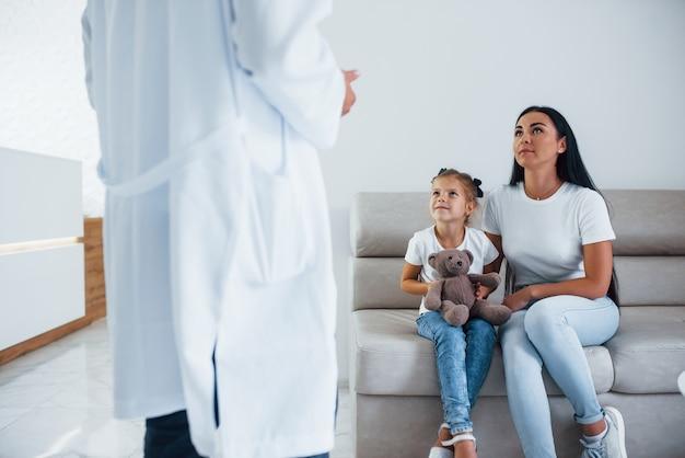 Matka z uroczą córeczką odwiedza klinikę. słucham lekarza.