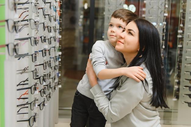 Matka z uroczym synem. rodzina kupuje okulary