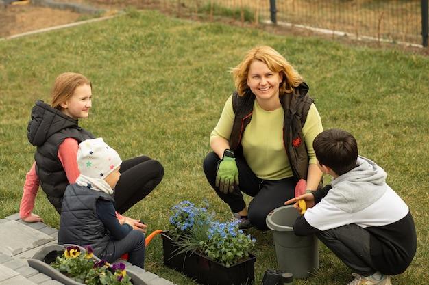 Matka z wieloma dziećmi sadzi kwiaty w doniczkach przed lub za domem. chętnie spędzam czas razem z rodziną