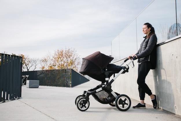 Matka z wózkiem lub spacerówką na nowoczesnych ulicach miasta