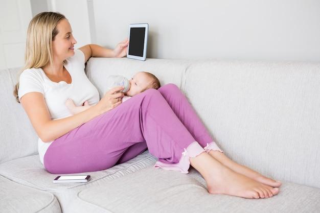 Matka za pomocą cyfrowego tabletu podczas karmienia dziecka butelką mleka