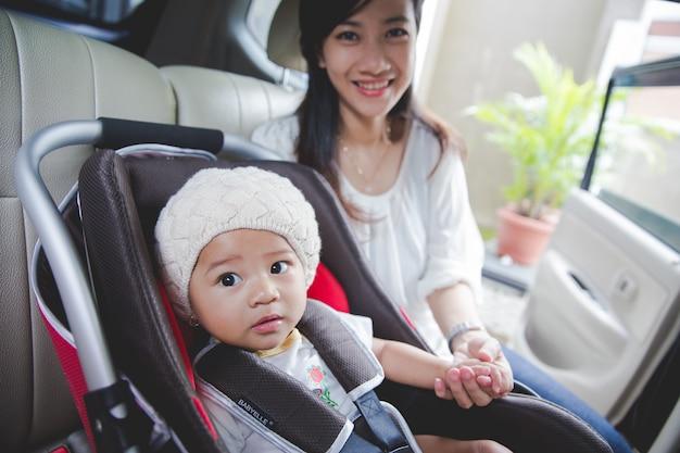Matka zabezpiecza swoje dziecko na siedzeniu w samochodzie