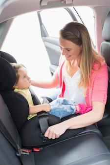 Matka zabezpiecza swoje dziecko w foteliku samochodowym