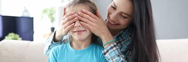 Matka zakrywająca rękami oczy córki mała dziewczynka trzyma pudełko z prezentem