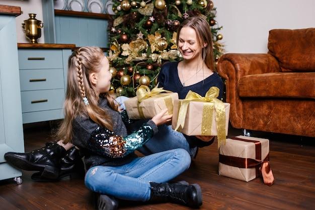 Matka zamierza zrobić córce niespodziankę w pobliżu choinki w domu.