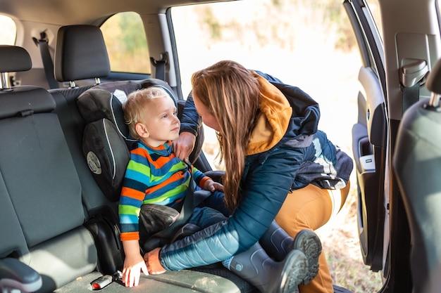 Matka zapina pas bezpieczeństwa dla swojego chłopca w foteliku samochodowym. bezpieczeństwo fotelika samochodowego dla dzieci