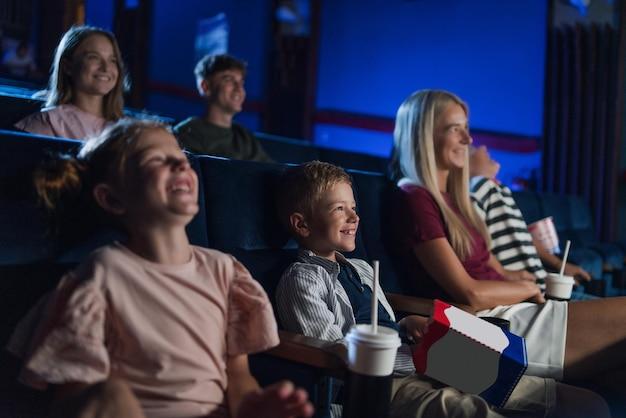 Matka ze szczęśliwymi małymi dziećmi w kinie, oglądająca film i śmiejąca się.