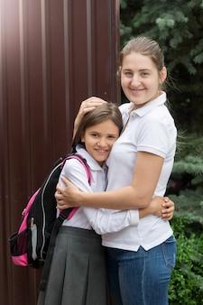 Matka żegna się z córką przed wyjściem do szkoły