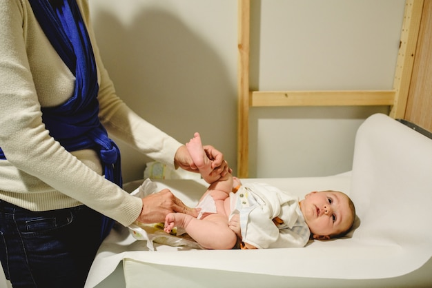 Matka zmienia pieluchę dla dziecka, wycierając ją wilgotną ściereczką.
