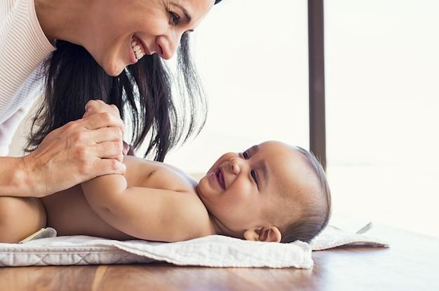 Matka zmienia pieluchę na małe dziecko