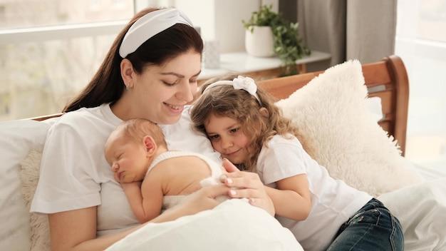 Matka zostaje w łóżku z noworodkiem i przytula się, całując córkę. piękna młoda mama z małą dziewczynką z kręconymi włosami i niemowlęciem śpiącym na jej klatce piersiowej. szczęśliwa rodzina portret