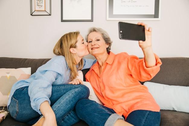 Matki i córka bierze selfie w żywym pokoju