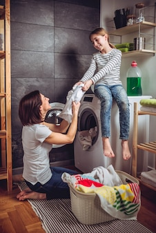 Matki i córki kładzenie odziewa w pralce