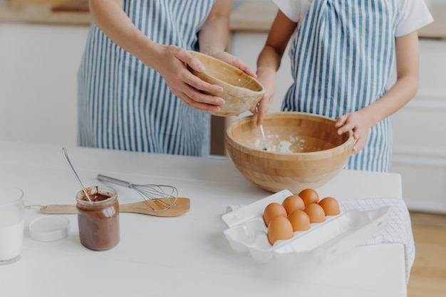 Matki i córki mieszają ręce, aby przygotować ciasto i upiec smaczne ciasto