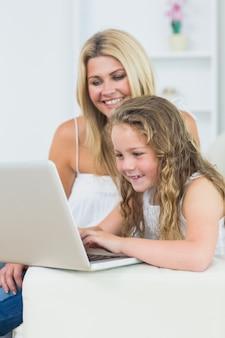 Matki i córki obsiadanie na kanapie z laptopem
