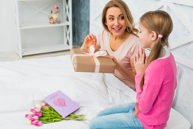 Matki i córki obsiadanie na łóżku z prezentem