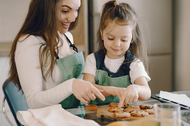 Matki i córki obsiadanie w kuchni z ciastkami