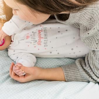 Matki i dziecka mienia ręki na łóżku