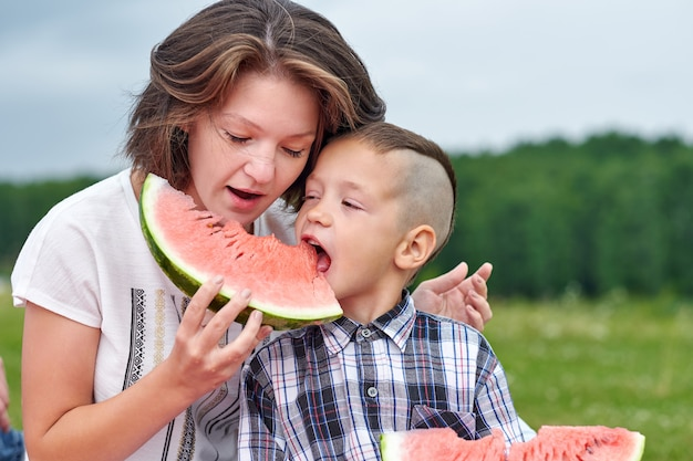 Matki i syna łasowania arbuz w łące lub parku. szczęśliwa rodzina na pikniku. portret na zewnątrz mały chłopiec i mama