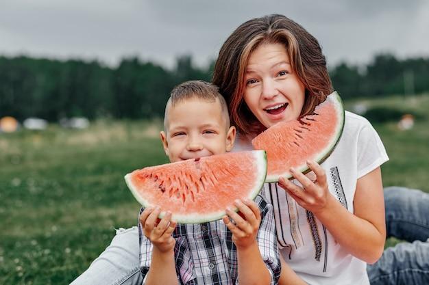 Matki i syna łasowania arbuz w łące lub parku. szczęśliwa rodzina na pikniku. portret na zewnątrz