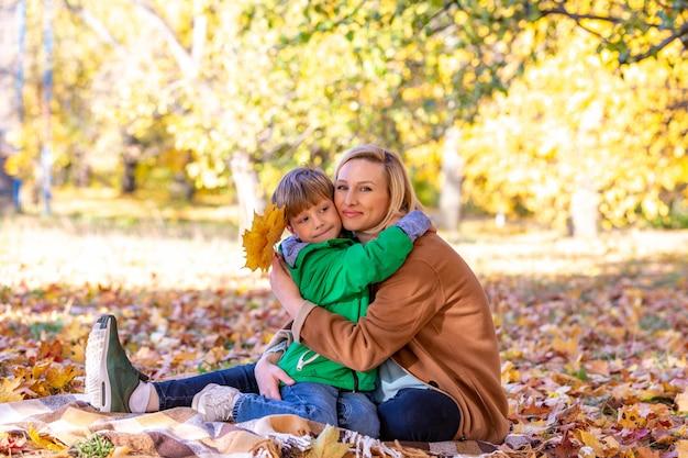 Matki i syna przytulenie wśród jesieni plenerowej. pojęcie przyjaźni syna z rodzicami, rodzina