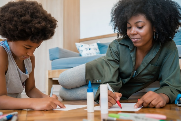 Matki i syna rysunek z barwionymi ołówkami na podłoga.