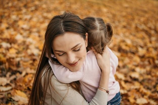 Matki kochają mamusie kochają zbliżenie portret obejmujący mamę i córeczkę malucha w jesiennym parku