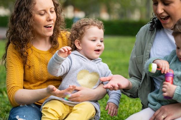Matki lgbt na świeżym powietrzu w parku ze swoimi dziećmi