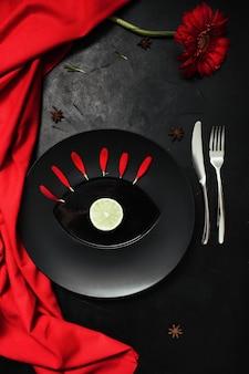 Matowy talerz na czarnym tle z czerwonym akcentem koloru. kreatywna koncepcja nakrycia stołu w restauracji
