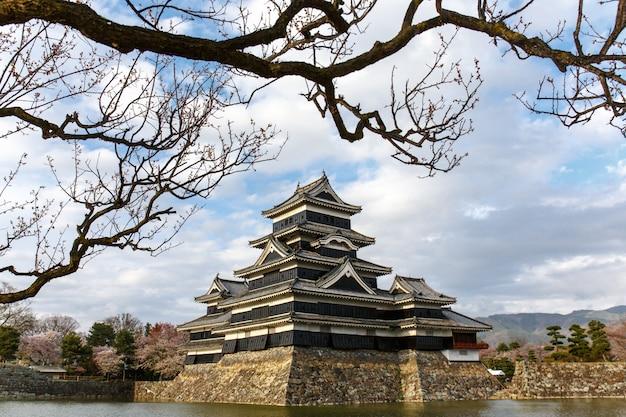 Matsumoto kasztel w wiosna sezonie otaczającym wodą pod obłocznym niebem