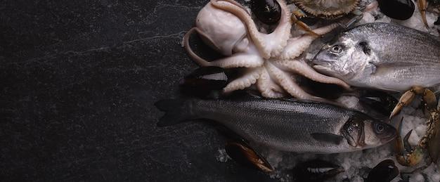 Mątwa, Okoń Morski, Małże, Dorado I Krab Błękitny Na Lodzie, Owoce Morza Na Marmurowym Stole Premium Zdjęcia