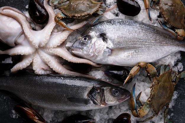 Mątwy, okoń morski, małże, dorado i niebieski krab na lodzie, owoce morza na marmurowym stole