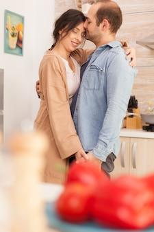 Mąż całuje czoło żony podczas tańca z nią w kuchni. miłość żony i męża, romans, czuła chwila, zabawa i szczęście w domu, wspólna muzyka wesoła i uśmiechnięta