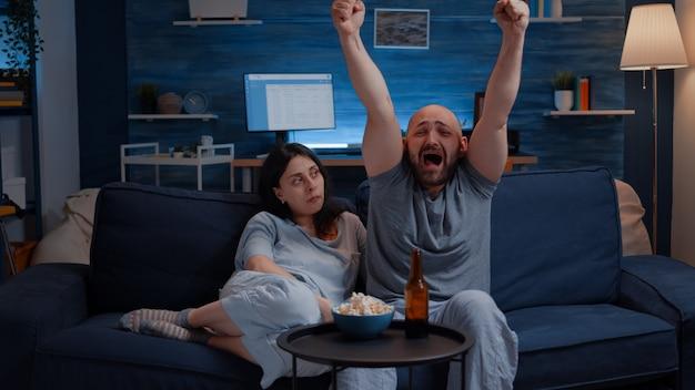 Mąż fan piłki nożnej ogląda mecz sportowy wspierający drużynę podnoszącą ręce po wygraniu zdenerwowanej żony sitt...