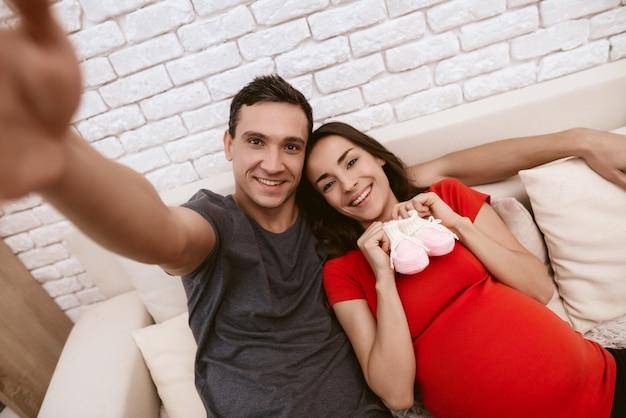 Mąż i ciężarna żona robią selfie.