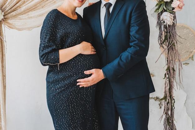 Mąż i ciężarna żona stojący trzymając brzuch