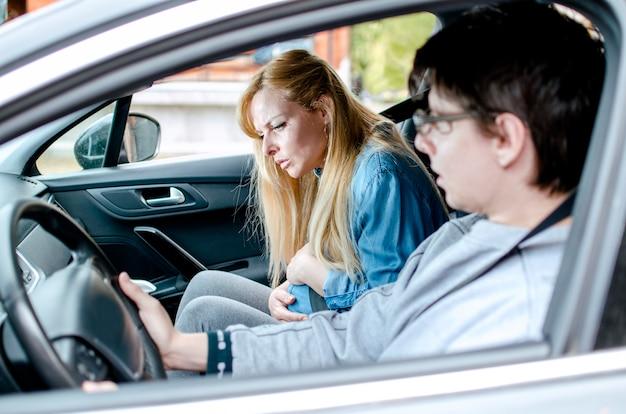 Mąż i jego ciężarna żona jadący samochodem ciężarna kobieta o bóle porodowe siedząca w samochodzie z chłopakiem młoda para jadąca do szpitala dla kobiety, która się rodzi. kobieta, która rodzi się w samochodzie