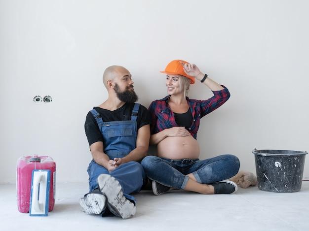 Mąż i jego ciężarna żona siedzą na podłodze w pokoju. mundur roboczy i pomarańczowy hełm ochronny. spójrz na siebie i uśmiechnij się. skopiuj miejsce.