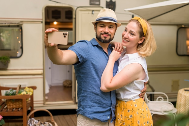 Mąż i żona biorący selfie podczas przytulania