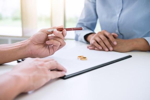 Mąż i żona czytają umowę rozwodową i podają pióro do podpisania dekretu o rozwodzie