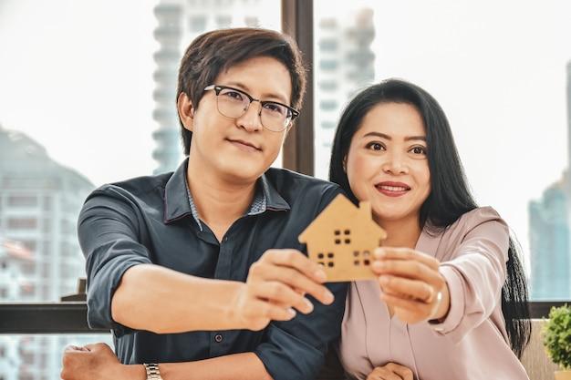 Mąż i żona kupują dom, z bliska ręka trzyma model domu