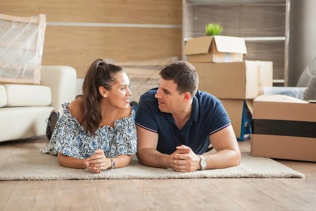 Mąż i żona leżą na podłodze po rozpakowaniu w swoim nowym domu