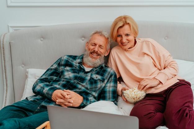 Mąż i żona oglądają na łóżku film i jedzą popcorn