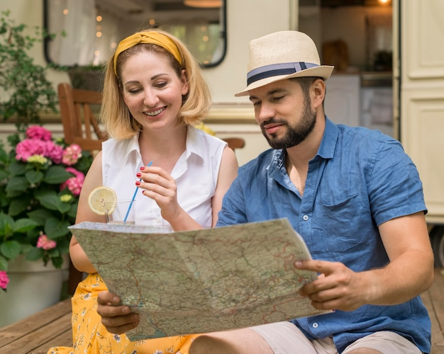 Mąż i żona patrzą na mapę obok swojej przyczepy kempingowej