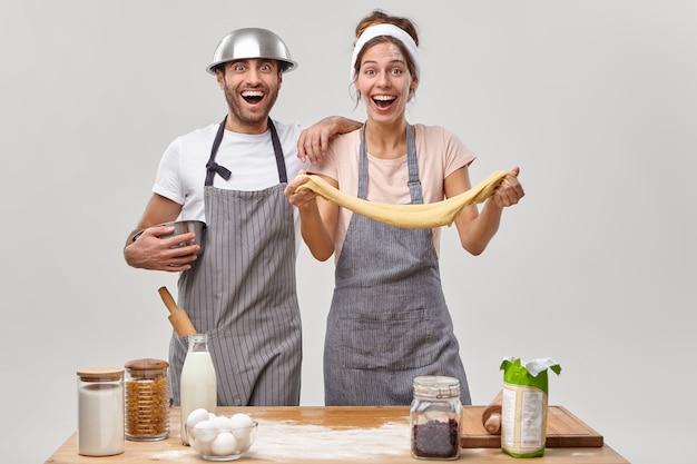 Mąż i żona pozują w kuchni przygotowując smaczny obiad