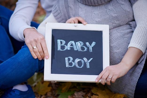 Mąż i żona trzymają znak dla chłopca