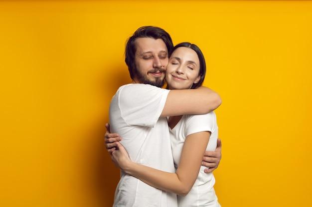 Mąż i żona w białych koszulkach stoją na żółtej ścianie
