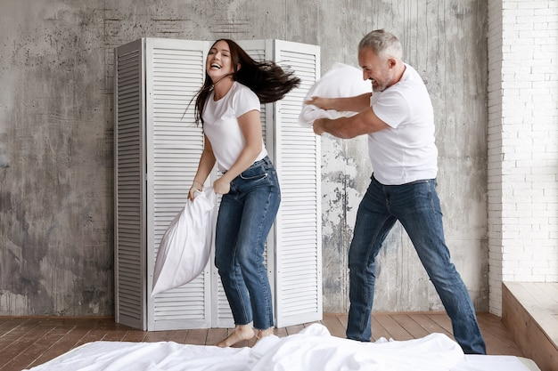 Mąż i żona walczą z poduszkami i śmieją się