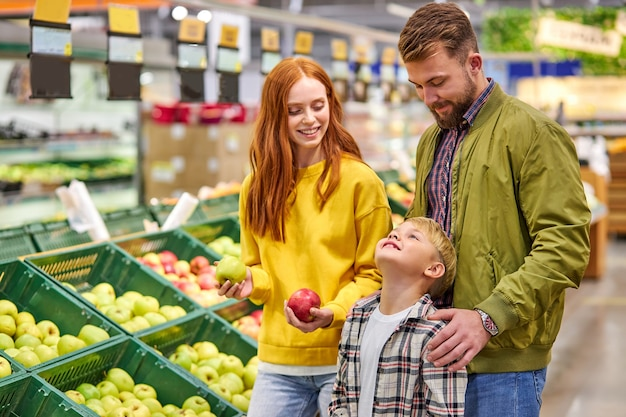 Mąż i żona z dzieckiem kupują owoce, jabłka. trzyosobowa rodzina wybiera świeże jabłko w dziale owoców supermarketu lub rynku