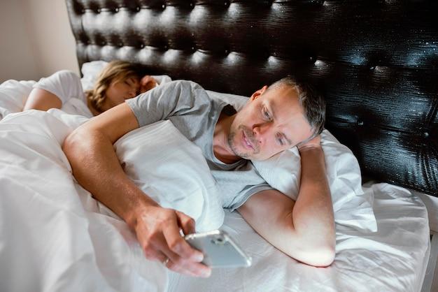 Mąż korzysta z telefonu komórkowego, gdy żona śpi